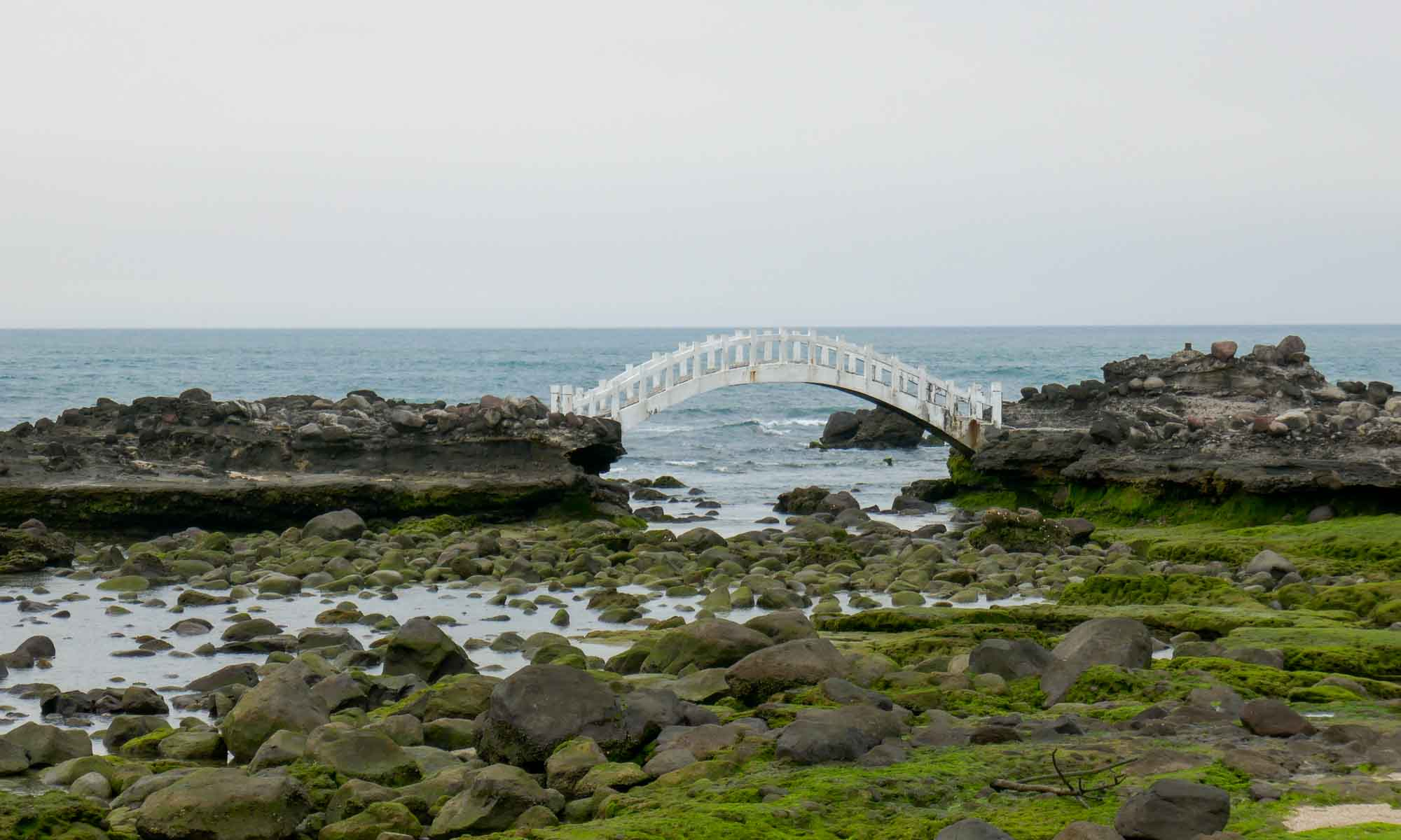 Small bridge in the sea behind the arch