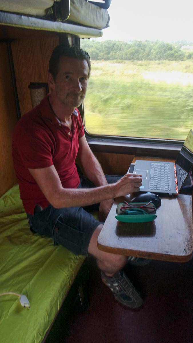 Working on the train while seated on our lime green camping sheet