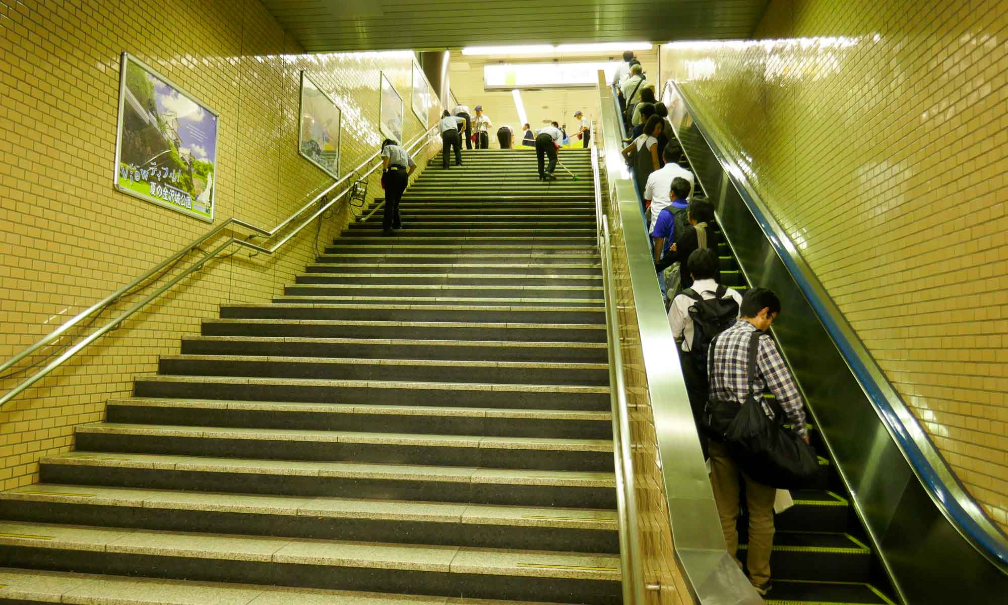 Cleaners cleaning the stairs and banisters in the Tokyo metro